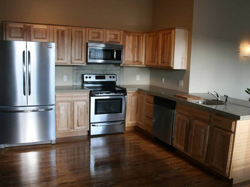 Big Lick Junction L kitchen with dark countertops hardwood floors and light wooden cabinets