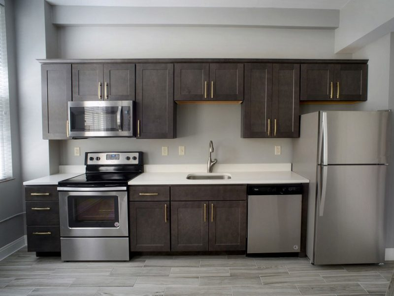 Boxley Building Kitchen hardwood floors, stainless steal appliances, and grey cabinets