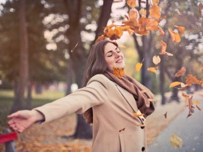 Dark haired woman standing under falling leaves in the fall