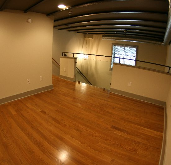 The Auction House loft bedroom with hardwood floor