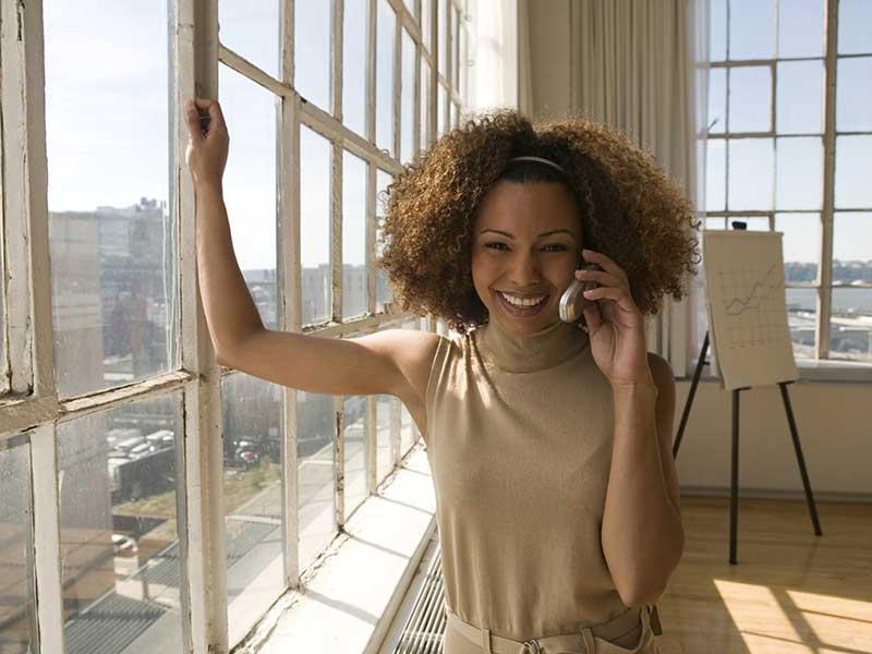 Woman standing near windows on her cellphone